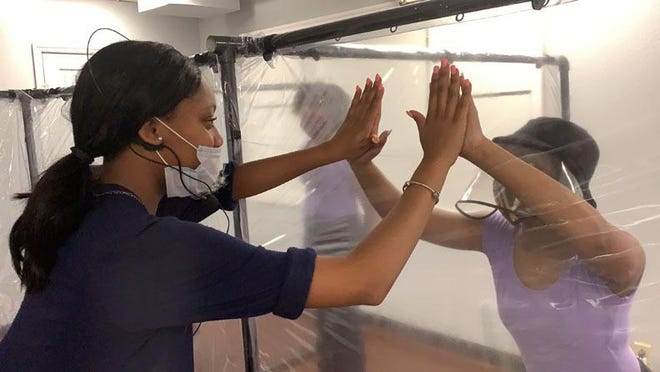 Rebecca Padgett School of Performing Arts teacher Quinyawna Miller gives Mariah Mims a safe double high five through the plastic of the new social distancing dance pods. The pods are see through to allow students and teachers to safely interact.