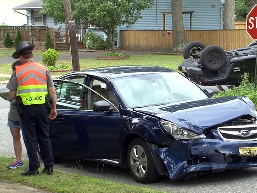 A Toms River police officer talks with one of the drivers involved in a collision at Larch Drive and Oak Hill Road in the township Thursday, June 19, 2014.  The driver of the overturned Jeep was medevaced to Jersey Shore University Medical Center.