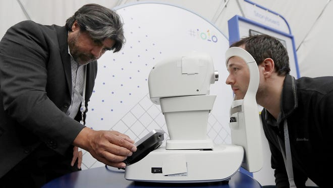Jorge Cuadros, left, gives a demonstration of a robotic retinal camera to a reporter at the Google I/O conference.