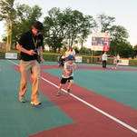 Volunteer buddy Joe Stokes runs with a Miracle League player stealing home. Volunteers are needed for the upcoming season.