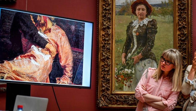 "Two journalists look at the screen showing the damaged world famous painting of the 16th century Russian Tsar, titled ""Ivan the Terrible and his Son Ivan on November 16, 1581."""