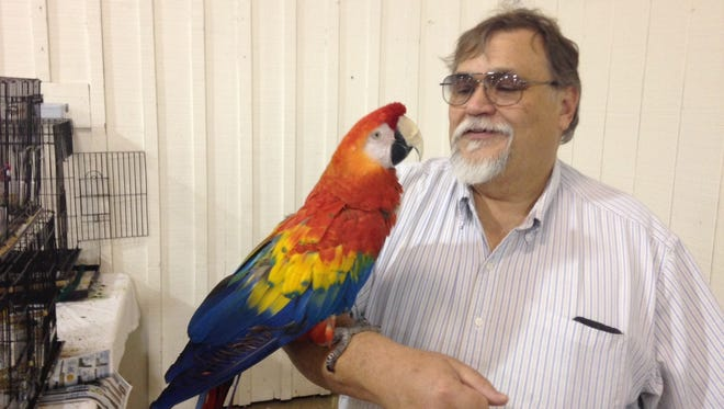 Michael Camire, of Bird Buffet N Things LLC, holds his scarlet macaw, Ria, at the Exotic Bird Fair at the Jackson Fairgrounds Sunday afternoon.