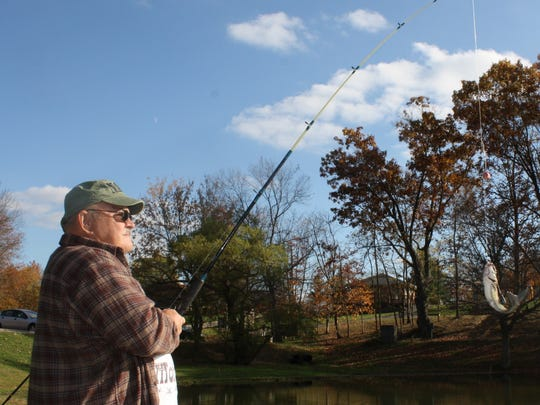Dick Miller, of Alexandria, reels in a catfish at Alexandria