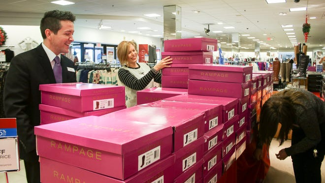 From left, Ashley Turner, Amber Lien and Ashley Holder stock shoes at Belk in Governors Square Mall. The store will be open Thanksgiving Day at 4 p.m.