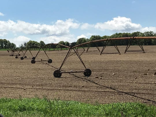 A center pivot irrigation system stands in a field west of Wautoma. Potato farmers in the central sands region of the state rely on high-capacity wells for large-scale irrigation.
