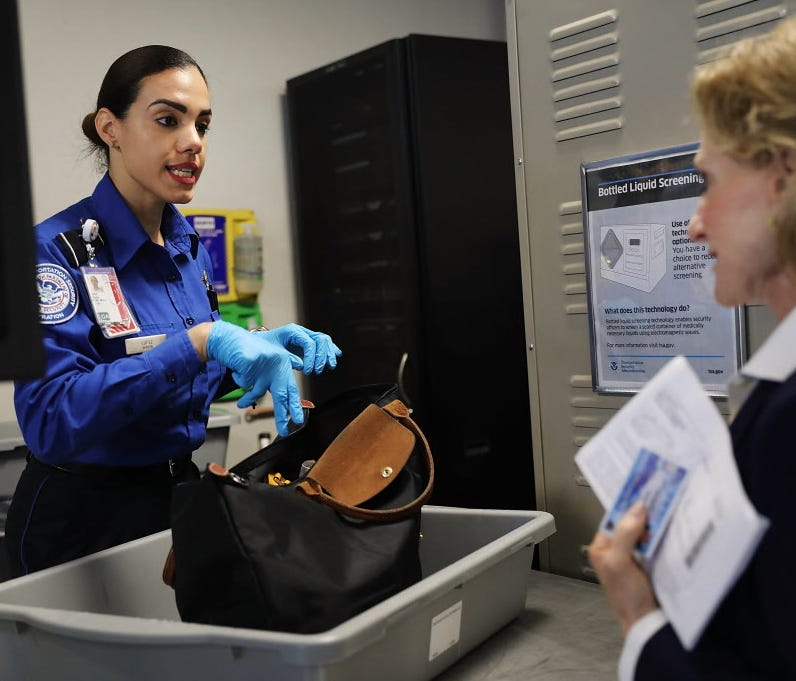 A Transportation Security Administration officer screens a carry-on bag at LaGuardia Airport on Sept. 26, 2017 in New York City.