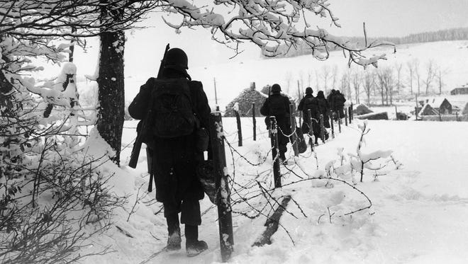 Troops of the 3rd U.S. Army march toward the village of Lutrebois, near Bastogne, Belgium in January 1945 during the Battle of the Bulge.