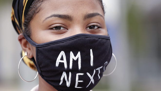 A demonstrator with a message on her mask stands quietly during a June 8 demonstration in Orlando to protest the killing of George Floyd.