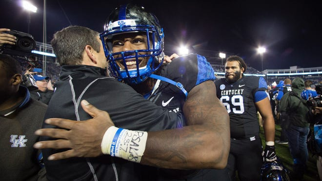 Kentucky defensive end Bud Dupree hugs athletic director Mitch Barnhart as he leaves the field after Kentucky beat South Carolina 45-38 in Lexington on Oct. 4.