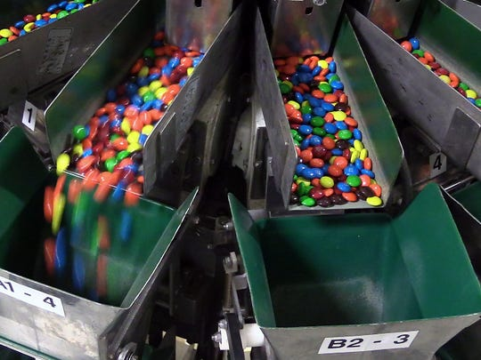 M&M's fall into a chute that sends them into individual packages at the Mars Chocolate plant in Hackettstown, N.J., on March 1, 2016. The M&M's brand turns 75 on Thursday.