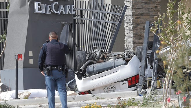 A Ford Mustang lies upside down, crashed into the fence near El Paso EyeCare, 8894 Gateway North Blvd. near Moonlight Avenue in Northeast El Paso on Friday afternoon. A Chapin High School student was killed in the accident.