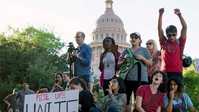 In this May 1, 2017, file photo, protesters against the Senate Bill 4 sanctuary cities ban rally outside the Texas Department of Insurance building where Republican Gov. Greg Abbott has an office in Austin, Texas.