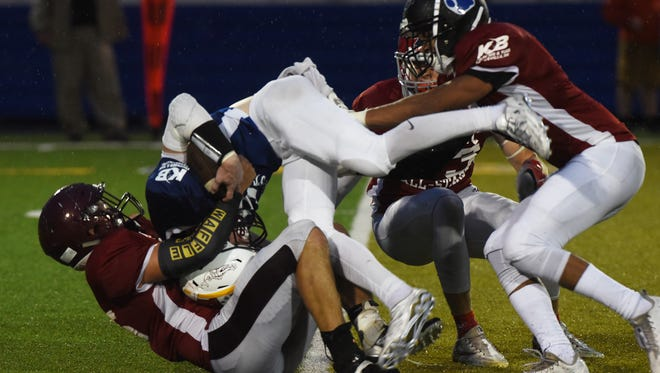 Watkins Memorial's Dante Fair, right, assists Licking Heights' L.A. Kelly in taking down the Muskingum Valley ball carrier for a loss during this past Friday's Licking-Muskingum All-Star Game.