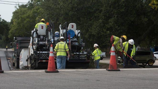 A resurfacing crew works on a street.