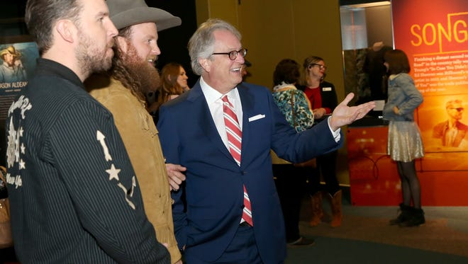 NASHVILLE, TN - MARCH 06:  (L-R) T.J. Osborne and John Osborne of musical duo Brothers Osborne and CEO of the Country Music Hall of Fame, Kyle Young, admire Country Music Hall of Fame and Museum new exhibition American Currents: The Music Of 2017 on March 6, 2018 in Nashville, Tennessee.  (Photo by Terry Wyatt/Getty Images for Country Music Hall Of Fame & Museum)