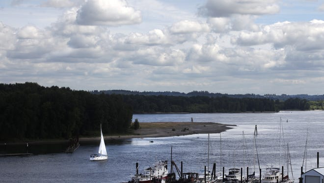A boat sails past Sand Island Marine Park in St. Helens. Columbia Riverkeeper and another group asked state authorities not to allow the re-classification of 837 acres of farmland for industrial use near the Port of St. Helens, north of Sand Island.