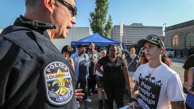 LMPD's Lt. Ron Heady talks with protesters on the sidewalk in front of Immigration and Customs Enforcement office in Louisville on Tuesday morning.  The city has made several requests of the protesters to keep the sidewalk clear.