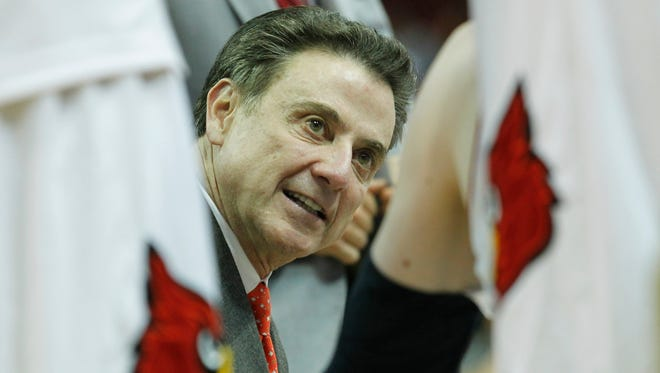 University of Louisville head coach Rick Pitino talks with his player during a time out against Savannah State during the second half of play at the KFC Yum! Center in Louisville, Kentucky, November 24, 2014.
