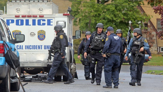 Members of the New Rochelle police critical incident unit gather on Lomond Place after a report of shots fired in the area Oct. 23, 2014. The report turned out to be unfounded; police concluded it was fireworks.