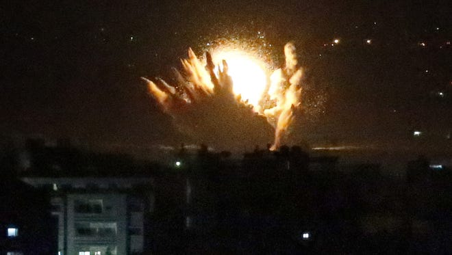 An Israeli missile hits Palestinian buildings in Gaza City on Thursday night.