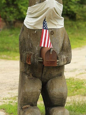 RUTLAND - A bear sculpture wears a mask on East County Road in Rutland on Monday.