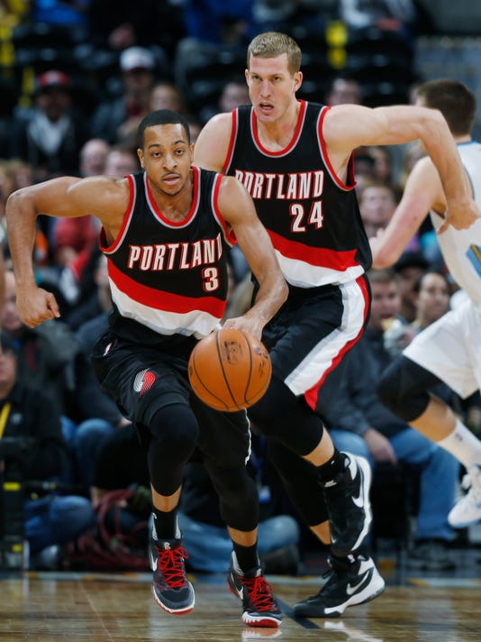 Portland Trail Blazers guard C.J. McCollum, front, picks up a loose ball as center Mason Plumlee follows down the court against the Denver Nuggets in the first half of an NBA basketball game, Sunday, Jan. 3, 2016, in Denver. (AP Photo/David Zalubowski)