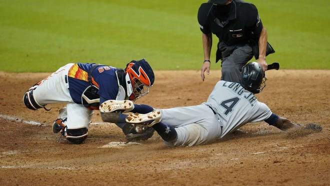 Seattle Mariners' Shed Long Jr. (4) scores as Houston Astros catcher Martín Maldonado reaches to tag him during the eighth inning of Sunday's game in Houston.
