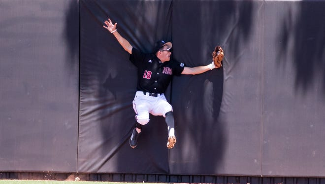 New Mexico State's Greg Popylisen makes the catch and crashes into the outfield fence for the out against Seattle Sunday afternoon at Presley Askew Field.