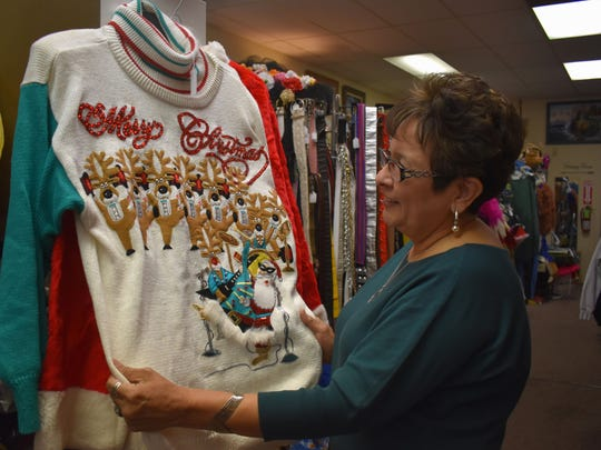 In this Daily News file photo, Martha Jones, employee at Vintage Etc., fixes a Christmas sweater on display during Small Business Saturday.