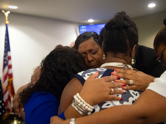 Karen Crosby, center, embraces four other black women