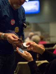 Jerry Nachison, hands out anti-border wall and pro immigrant buttons before the Las Cruces City Council Meeting, where a resolution opposing the constrution of the proposed border wall with Mexico was read and voted on. Tuesday February 21, 2017.