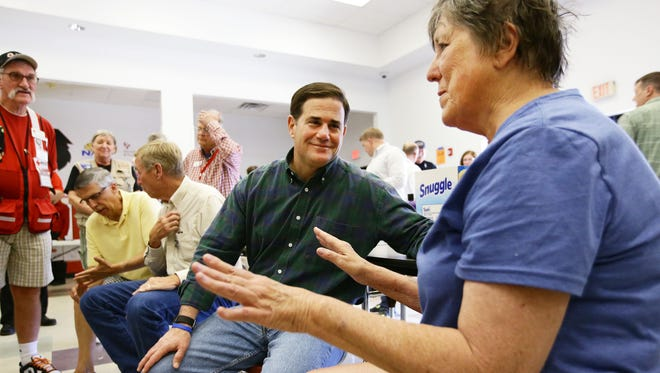 Arizona Gov. Doug Ducey talks with Jean Wilson, an evacuee from the community of Pine Flats, during his tour of the Goodwin Fire on June 29, 2017, in Mayer.