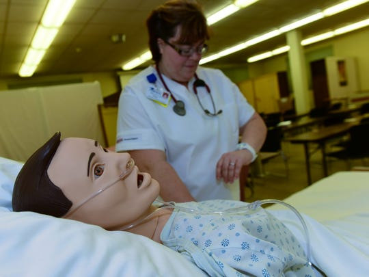 Dory Thomas checks a 'patient's' pulse during class Monday, Dec. 21, 2015 in the Franklin County Career and Technology Center Practical Nursing Program at Wilson College.