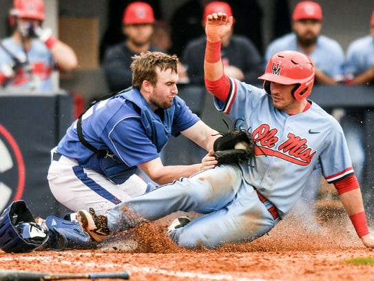 Ole Miss' Nick Fortes, right, is tagged out by Eastern