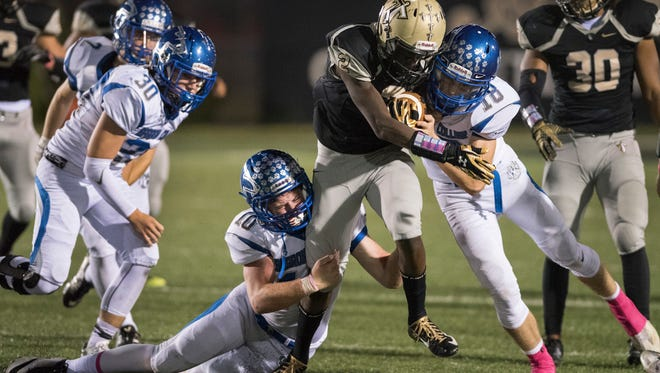 Jouvensly Bazile of Golden Gate is tackled by Kevin Thorne (10) and Michael MclLy of Barron Collier during the game at Golden Gate High School Friday night, Oct. 14, 2016.