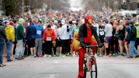 Dressed up as a turkey, Tim Fulton of West Manchester Township rides his bicycle ahead of the start line at the YMCA of York County's 18th annual Turkey Trot 5K race on Thursday, Nov. 27, 2014. Fulton rode ahead of the lead runners the entire race. About 4,700 people pre-registered for the YMCA of York County's 18th annual Turkey Trot 5K, whose route included sections of West Market Street, South George Street and the perimeter of Penn Park in York.