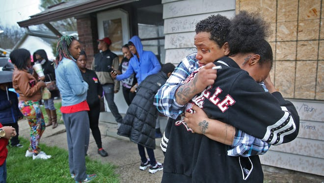 Brea Hutchison and Micheana Smith hug at an emotional remembrance Thursday, March 24, 2016, one year after a quadruple homicide in the 3100 block of North Harding Street. Smith lost several family members, including her mother, in the unsolved murders.