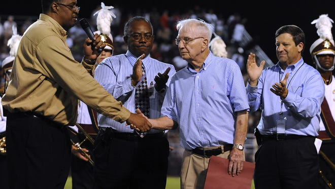 Pensacola High School Principal David Williams shakes hands with legendary former Pensacola High football coach Jimmy Haynes on Sept. 3,,2009 during the dedication of the new Pensacola High Jimmy Haynes Field House named in his honor.  The dedication took place at halftime in the game between PHS and Piine Forest. Also shown in the picture is Escambia County Deputy School Superintendent (background center) Norm Ross and, far right, Escambia County School Superintendent Malcolm Thomas.