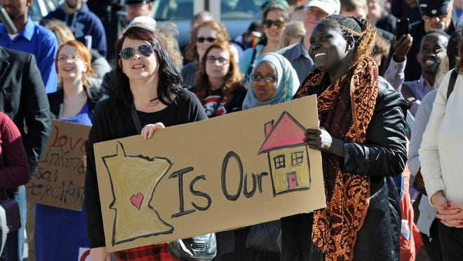 People hold signs while listening to speakers during an anti-racism rally and march in Oct., 2104, at the Stearns County Courthouse in St. Cloud.