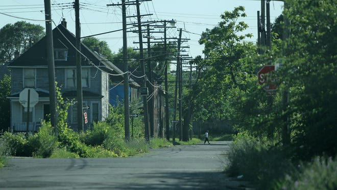 A man walks through the Delray neighborhood of Detroit in July, 2015. Last year, the Michigan Department of Transportation started to buy residential and commercial properties in the neighborhood for the Gordie Howe International Bridge project.