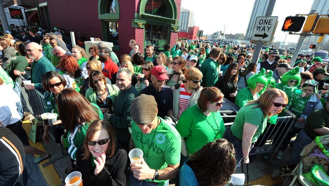 People pack the sidewalk area near the Elbow Room on Pennsylvania Street before the start of the 29th Annual St. Patrick's Day parade in downtown Indianapolis on Tuesday, March 17, 2009.