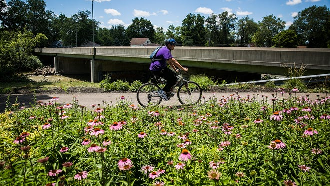 A cyclist rides along the White River Greenway near McCulloch Park in this file photo.