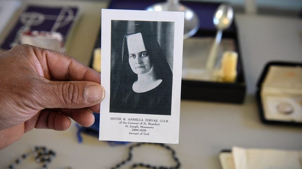 Patrick Norton holds a photograph of Sister M. Annella