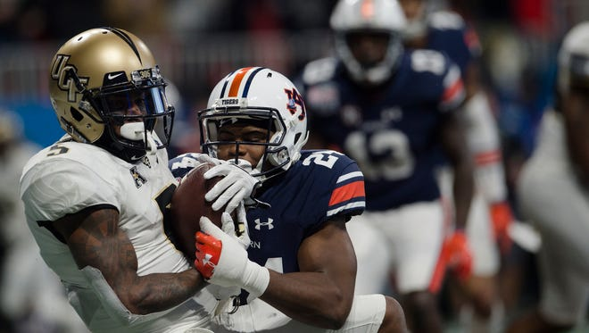 UCF wide receiver Dredrick Snelson (5) catches a touchdown pass to put UCF up on Auburn in the fourth quarter as Auburn defensive back Daniel Thomas (24) attempts to stop him during the second half of the Peach Bowl between Auburn and UCF on Monday, Jan. 1, 2018, at Mercedes-Benz Stadium in Atlanta, Ga.