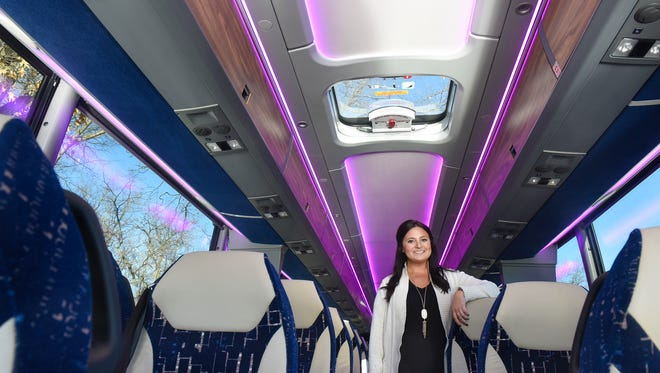 Trobec's Bus Service Vice President Bethany Schubert is surrounded by purple accent lighting in one of the company's coaches that will be used to transport families of football players during the Super Bowl in Minneapolis.