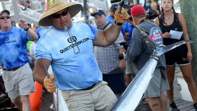 Alex Davis, a weigh master, holds a 63.5-pound white marlin from the White Marlin Open in Ocean City, Maryland.
