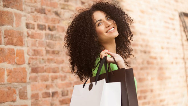 African american woman smiling with shopping bags outdoors