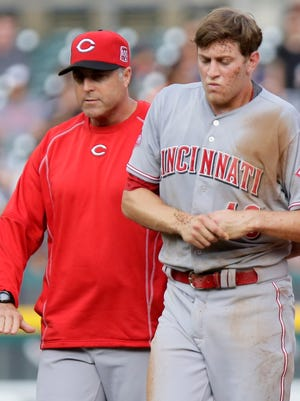 Pitcher Jon Moscot of the Cincinnati Reds is helped off the field by manager Bryan Price, left, after injuring his left arm while making a diving tag on Anthony Gose of the Detroit Tigers at second base during the first inning on June 15, 2015 in Detroit.