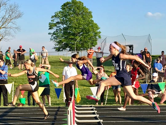 Mount Gilead's Allison Johnson, center, runs to a state berth in the 300 hurdles at Friday night's Division III regional championship at Fairfield Union.