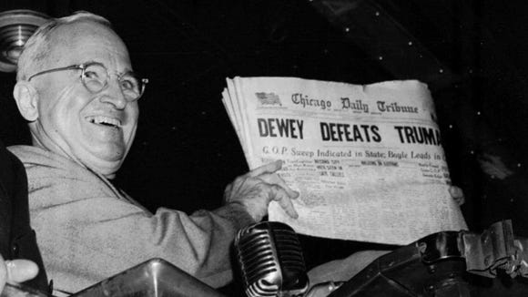 President Harry S. Truman holds up a copy of an election